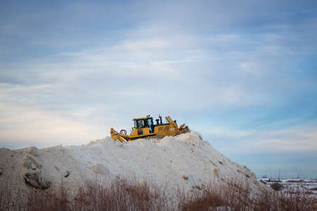 Large tractor grader pushing and piling snow up a huge snow hill Stok Fotoğraf