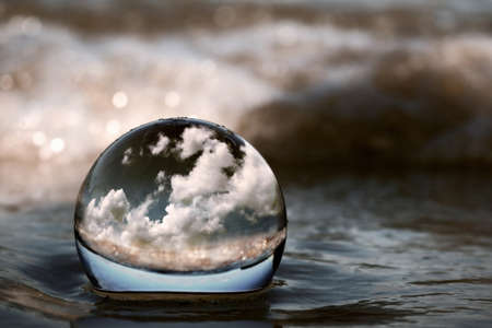Summer clouds displayed through a transparent glass ball on the beach sand