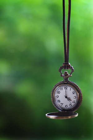 Brass pocket watch hanging from a leather rope Standard-Bild - 117300174