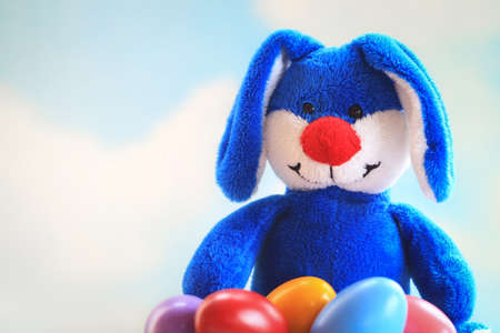 Cute blue bunny holding a bunch of colored easter eggs in his lap