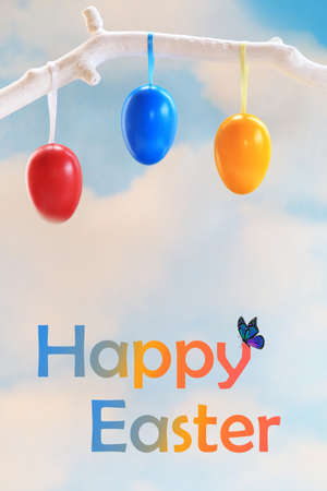 Easter eggs hanging from a white tree branch with the words happy easter