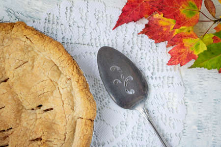 Fresh baked crab apple pie displayed with autumn leaves