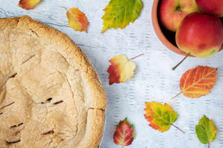 Fresh baked crab apple pie displayed with apples and autumn leaves