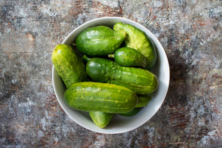 Bowl of garden cucumbers on rustic wood background