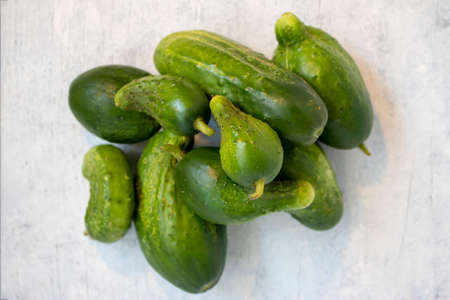 Stack of garden cucumbers on white wood background