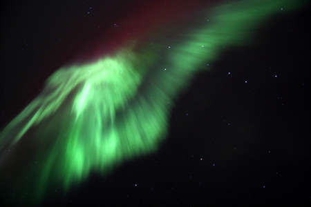 northern light: A green and red aurora dances overhead with the big dipper in the background  Stock Photo