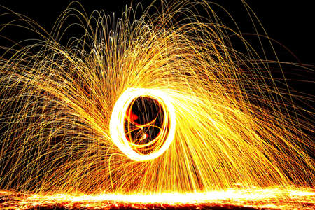 ignited: Ignited steel wool spun around forms a circle and releases sparks  Stock Photo
