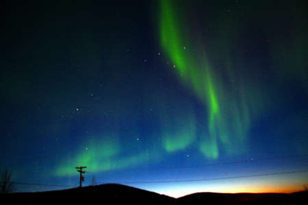 northern light: The aurora dances overhead to form a backwards  L  in the sky
