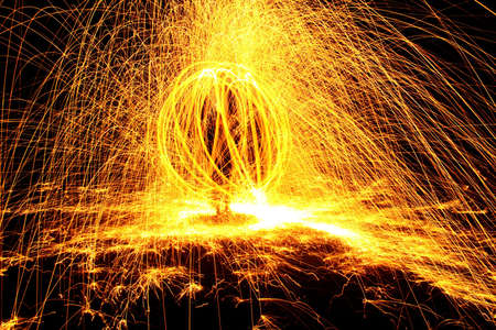 ignited: Ignited steel wool spun around forms a sphere and releases sparks