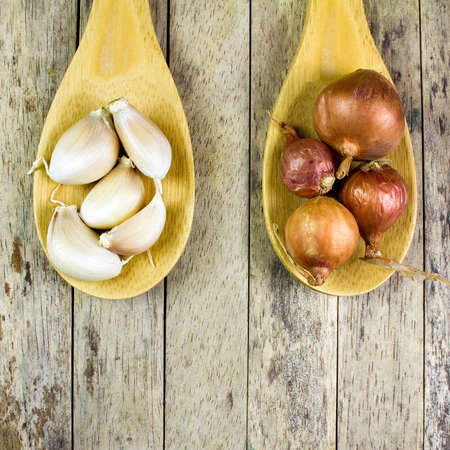 cebolla: cebollas y ajos en cuchara de madera, vista desde arriba, cuadrado recortado Foto de archivo