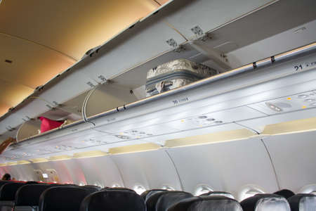 cabin baggage overhead on the airplane Stock Photo