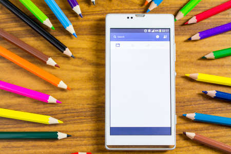 feed: BUNGKAN, THAILAND - NOVEMBER 10, 2015: smart phone with news feed Facebook on screen and color pencil around