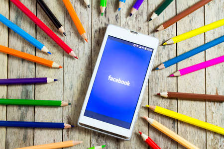 BUNGKAN, THAILAND - NOVEMBER 10, 2015: smart phone with facebook logo on screen and color pencil around Editorial