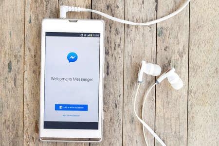 Messenger: BUNG KAN, THAILAND - MARCH 22, 2016: smart phone display facebook messenger app with earphones on wood background
