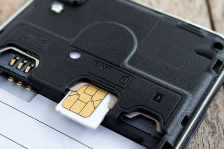roaming: sim card in slot of smart phone, soft focused
