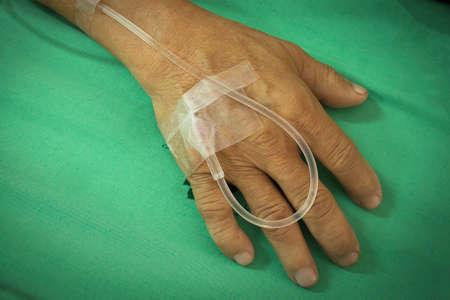 intravenous: old man hand is receiving patient intravenous saline, vignette corner