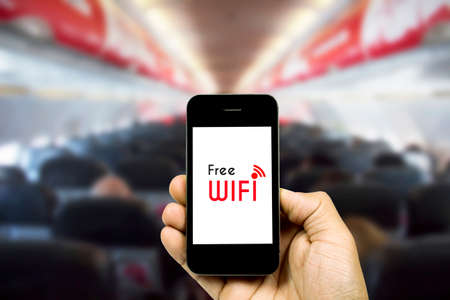hands free device: people holding smart phone on blurred cabin crew airplane background