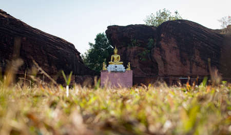 Gold buddha with big rock on background, blurred foreground