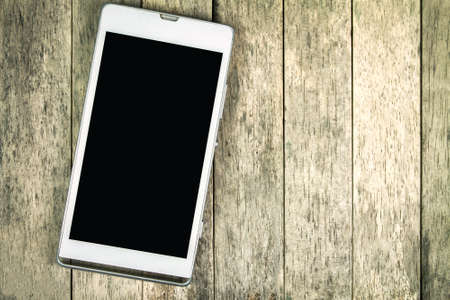 smart phone display empty screen on darken wooden background