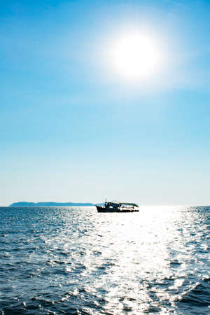 silhouette fishing boat in the ocean with sun and blue sky, back light with vignette Stock Photo