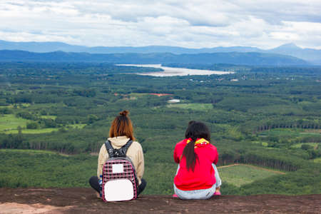 two woman friend sitting on the top of the mountain