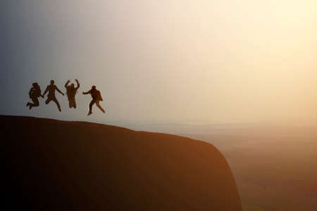 silhouette group of young jumping on the top of the mountain, copy space