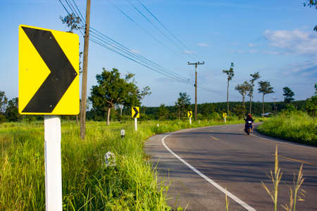 curve warning sign in the rural road, blurred man face Stock Photo