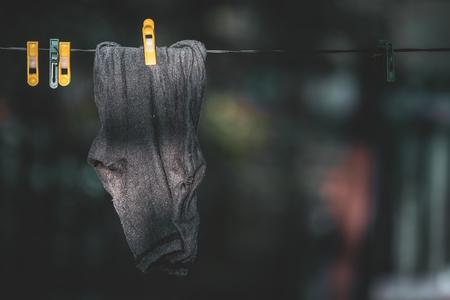 Schwarze Socken hängen trocknend an der Wäscheleine