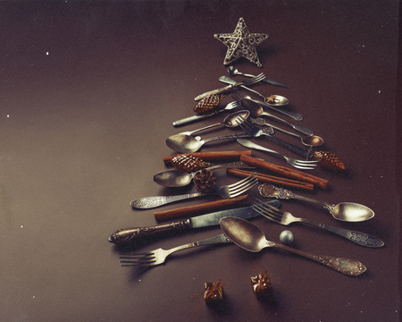 concept of an old vintage card. Abstract Christmas tree made from cutlery on a dark brown background.