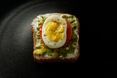 sandwich on black background. bread, egg avocado