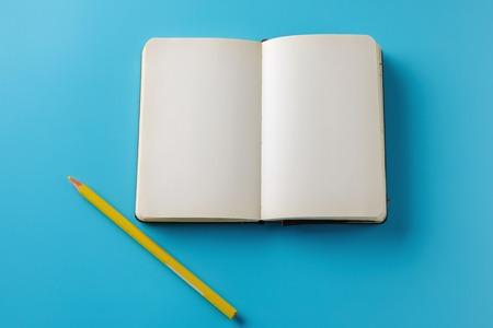 Maqueta Página en blanco con lápiz amarillo. Vista superior con espacio de copia para ingresar el texto. Lay Flat, fondo de color azul.