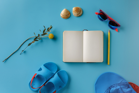 Summer childrens clothes and notebook on a bright blue background, top view.