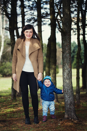 happy mother holding her little son by the hand in the park. woman and little boy in the forest. Imagens