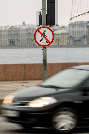 A persons road sign is forbidden. The road with the car and the sign on the street pass man is forbidden