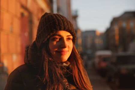A girl in a warm hat at sunset. Portrait in the City