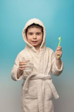 the boy brushes his teeth. A child in a robe with a toothbrush and a glass of water on a blue background. Zdjęcie Seryjne - 142504287
