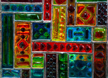 Multicolored stained glass window with an abstract pattern of bright colors