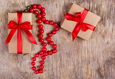 Surprise with a red bow and a necklace of coral on the old wooden background. Copy space.