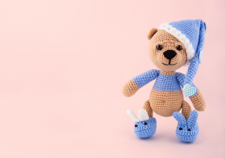 Knitted Teddy Bear In A Cap And Slippers On A Pink Background