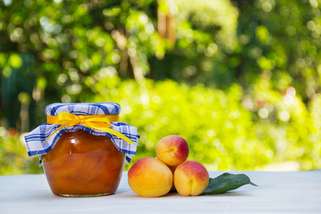 Homemade jam on a green natural background. A jar of home apricot jam and fresh apricots on a white table. Stock Photo