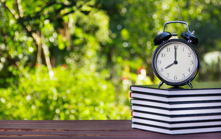 A stack of textbooks and a clock on a wooden table. A stack of books and an alarm clock on a green blurred background. Educational concept. School and lessons.