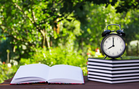 A stack of textbooks and a clock on a wooden table. Homework and education.