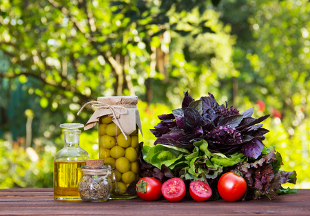 Ingredients for summer salad. Olives, basil, tomatoes and olive oil on the table. Green olives in a glass jar.