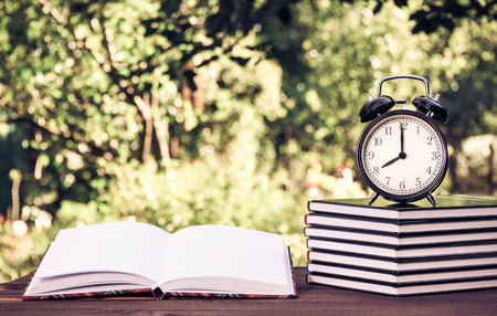 A stack of textbooks and a clock on a wooden table. Homework and education. Vintage tinting