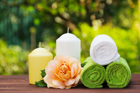 A stack of rolled towels, candles and fragrant roses. Spa concept. Spa set in the summer garden.