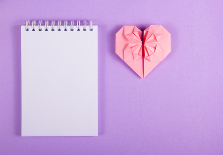 Open notebook with a blank page and origami heart. Valentine paper. Pink paper heart. St. Valentines Day. Copy space.