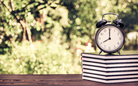 A stack of books and an alarm clock on a green blurred background. Educational concept. School and lessons. Vintage tinting