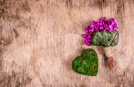 Spring flowers and heart from moss. Romantic bouquet with heart. Delicate violets and heart. Copy space.