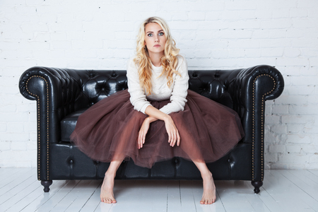 Elegant young woman in lush skirt sits on the couch. Concept fatigue