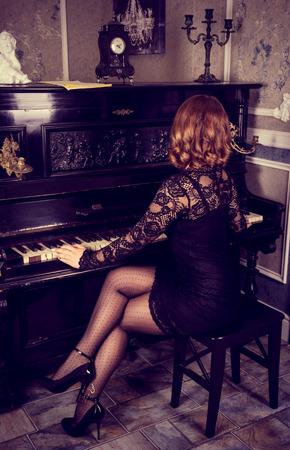 Mujer elegante vestida de negro tocando el piano. Hermosas piernas femeninas en medias y tacones.